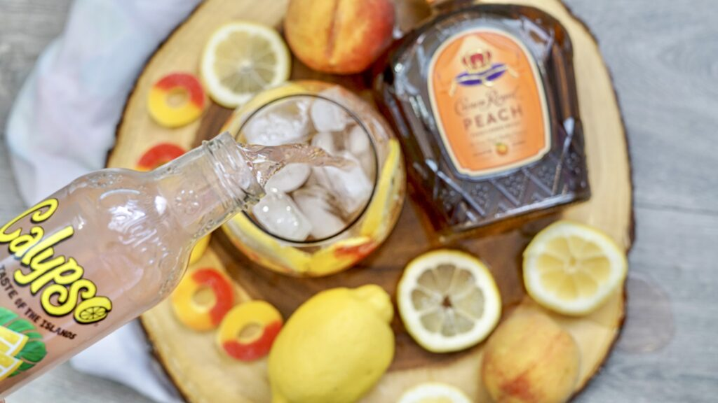 pouring peach lemonade into crown royal peach whiskey drink