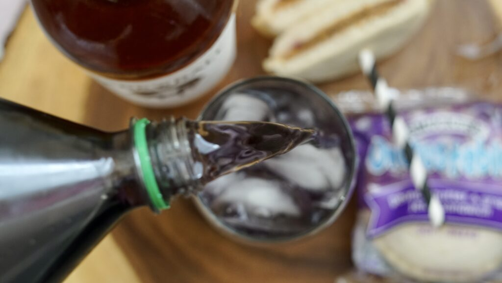 pouring grape soda into glass with peanut butter whiskey