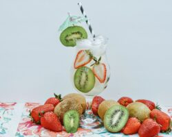 Fill a glass with ice cubes, kiwi slices & strawberries.