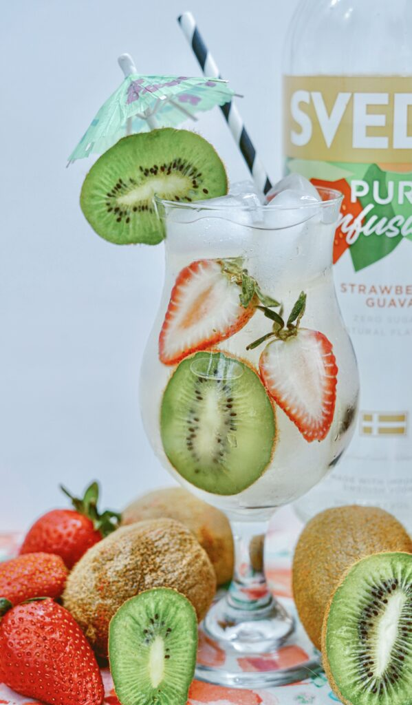 glass with ice cubes, kiwi slices & strawberries.
