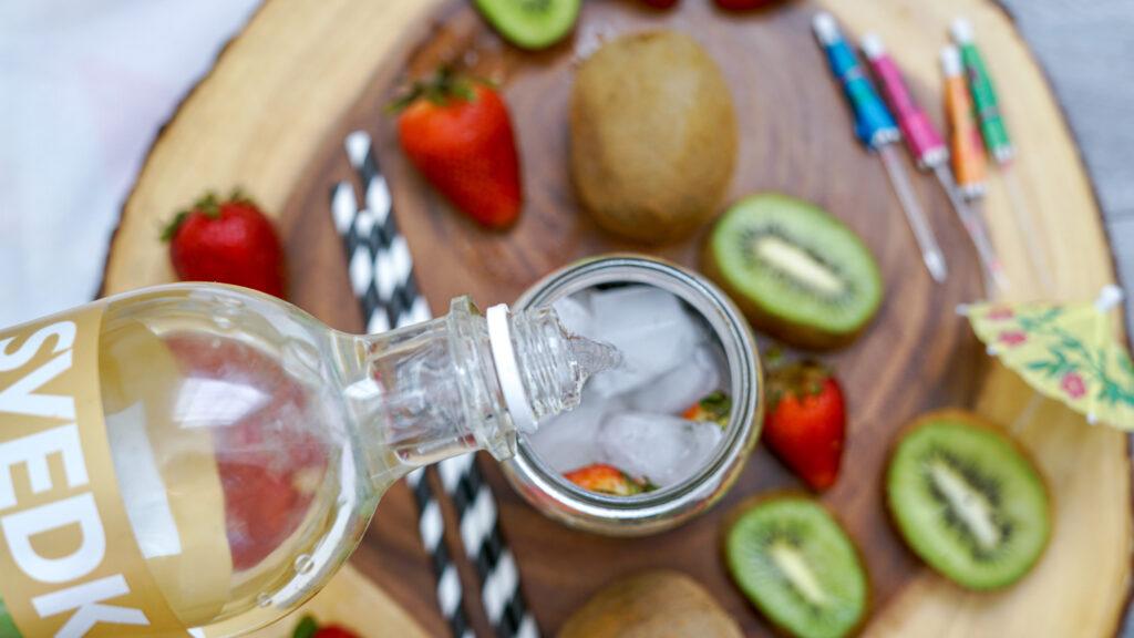 pouring strawberry vodka in glass