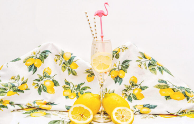 spiked lemonade mimosas on counter with lemonade towel and pink flamingo straw